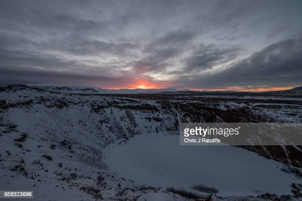 The sun sets behind the frozen volcanic crater lake Kerid on March 27 2017 near Selfoss Iceland Iceland's economy has been booming after an economic...