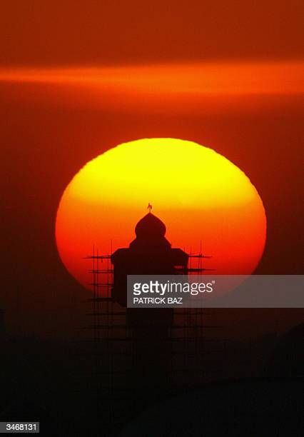 The sun sets behind the minaret of Shiekh Maarouf mosque in Baghdad 26 April 2004 At least three US soldiers and 13 Iraqis were killed across the...