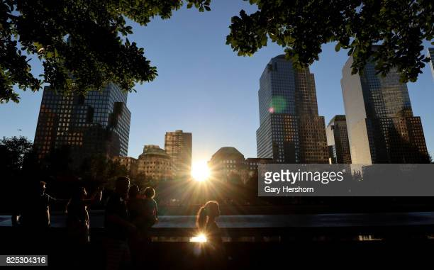 The sun sets behind the National September 11 Memorial in New York City on July 30 2017