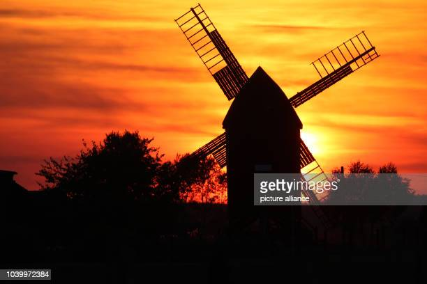 The sun sets behind the old wind mill 'Sommerfeld' inTiefenseeGermany 02 October 2013 The wind mill was built in 1847 and has been owned by the...