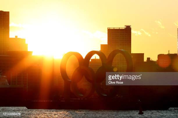 The sun sets behind the Olympic rings in Odaiba marine park on March 24, 2020 in Tokyo, Japan. Although an official decision is yet to be announced,...