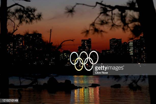 The sun sets behind the Olympic rings installation at Odaiba Marine Park on March 18, 2020 in Tokyo, Japan.