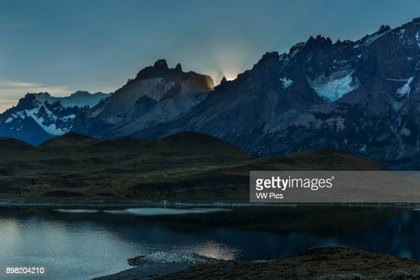 The sun sets behind the Paine Massif with the tip of La Mascara the Mask framed by sun rays Snowcapped Cerro Paine Grande is in the background with...