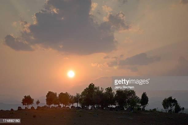 The sun sets behind the Plain of Jars Site 3 near Phonsavan