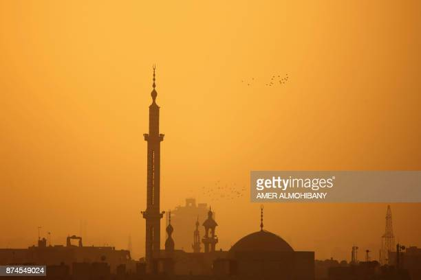The sun sets behind the rebel-held besieged town of Arbin, in the Eastern Ghouta region on the outskirts of Damascus, on November 15, 2017. / AFP...