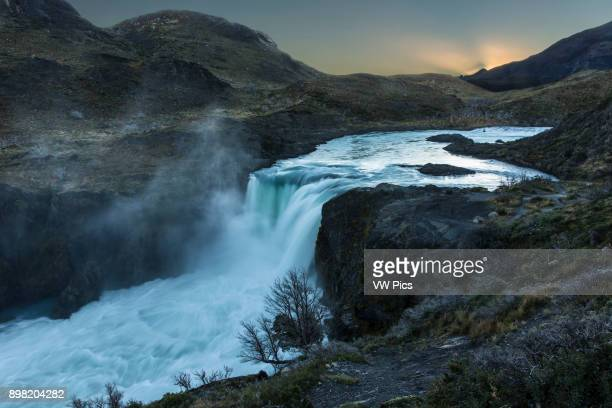 The sun sets behind the Salto Grande Waterfall on the Rio Paine or Paine River in Torres del Paine National Park in Patagonia Chile A UNESCO World...