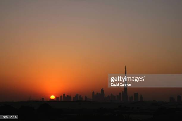 The sun sets behind the skyline of Dubai and the World's tallest building The Burj Dubai from the balcony of the clubhouse at the Four Seasons Golf...