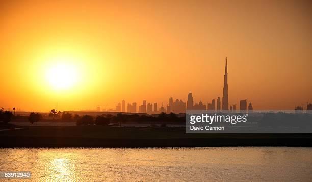The sun sets behind the skyline of Dubai and the World's tallest building The Burj Dubai and the par 315th hole at the Four Seasons Golf Club at...