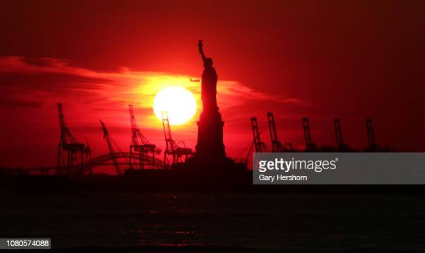 The sun sets behind the Statue of Liberty from Battery Park on December 10 2018 in New York City