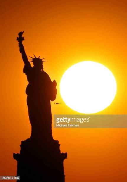 The sun sets behind the Statue of Liberty on June 02 2017 in New York City