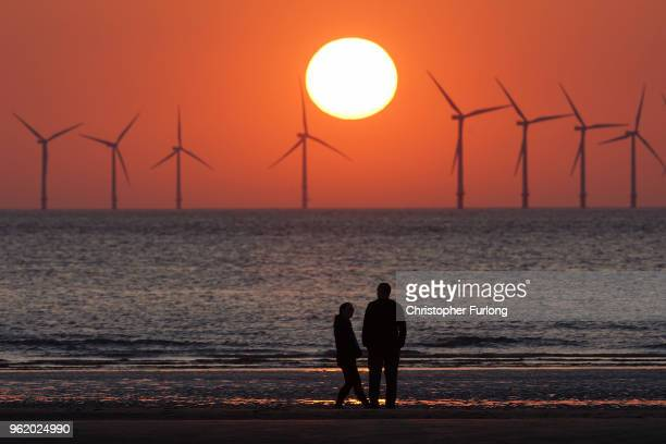 The sun sets behind the wind turbines of Burbo Bank Offshore Wind Farm in the Irish Sea on May 23 2018 in Wallasey England