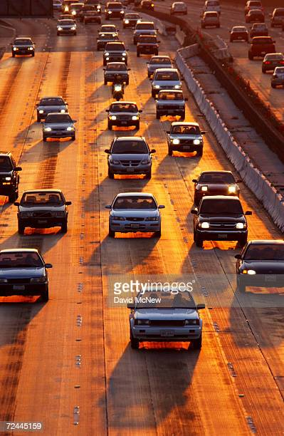 The sun sets behind traffic in southbound lanes of Highway 101 during a lighter than usual commute east of Hollywood on July 29 2002 in Los Angeles...