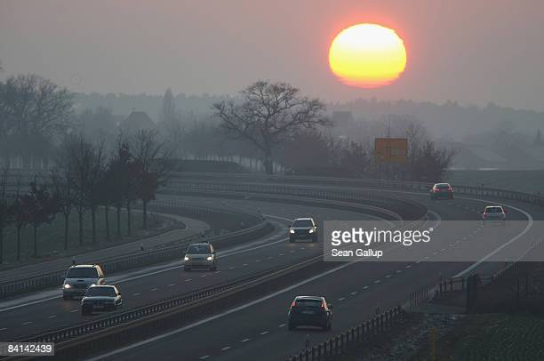 The sun sets behind traffic on a highway on December 30 2008 in Berlin Germany World oil prices rose sharply to over USD 41 a barrel in London...