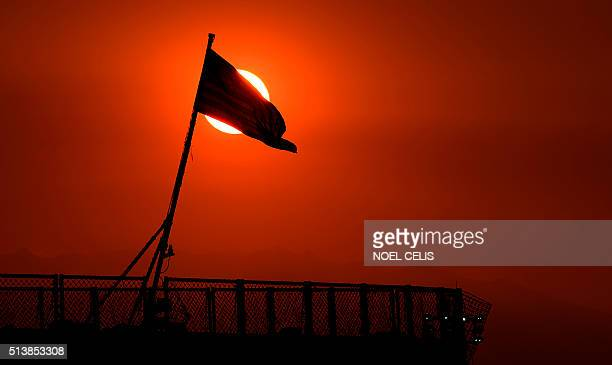 The sun sets behind US Navy ship USS Blue Ridge docked at the Manila Pier in Manila on March 5 2016 Blue Ridge is the oldest deployable warship of...