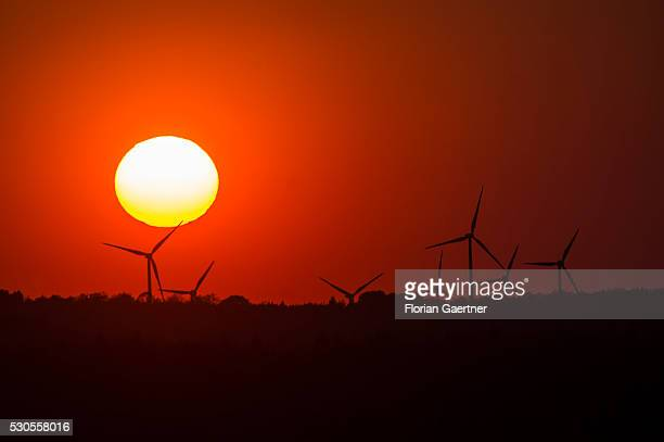 The sun sets behind wind turbines on May 07 2016 in JauernickBuschbach Germany