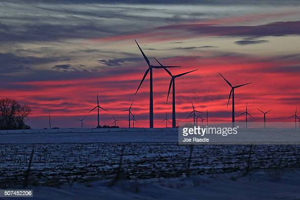 The sun sets behind wind turbines which the state uses to create nearly 30 percent of all electricity generated on January 29, 2016 in Fenton, Iowa....