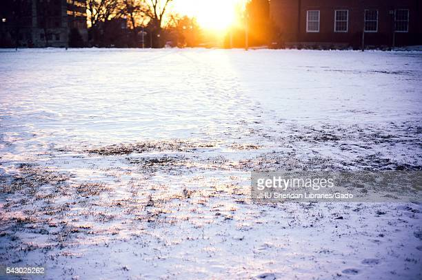 The sun sets between academic buildings on the snowy Homewood campus of the Johns Hopkins University in Baltimore, Maryland, 2015. Courtesy Eric...
