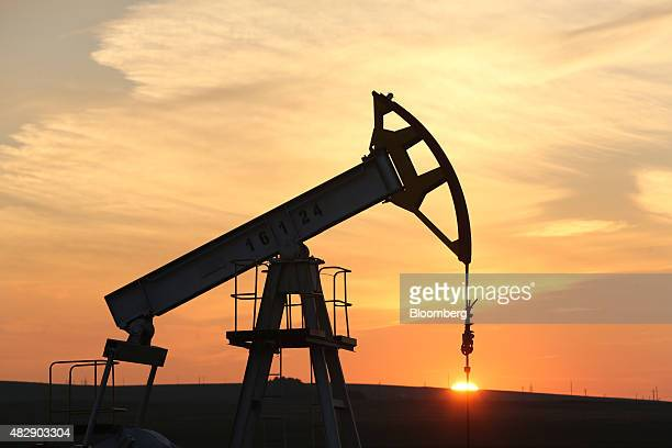The sun sets beyond an oil pumping unit also known as a 'nodding donkey' or pumping jack at a drilling site operated by Tatneft OAO near Almetyevsk...