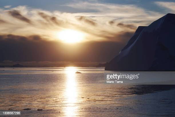 The sun sets beyond Icebergs which calved from the Sermeq Kujalleq glacier float in the Ilulissat Icefjord on September 05, 2021 in Ilulissat,...
