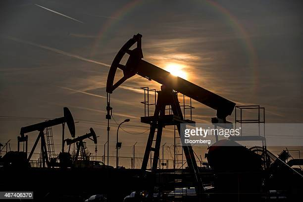 The sun sets beyond oil pumping units also known as nodding donkeys or pump jacks at an oil plant operated by MND AS in Uhrice Czech Republic on...