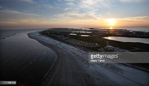 The sun sets beyond the beach as waves wash up from the Gulf of Mexico April 13 2011 in Grand Isle Louisiana Oil from the BP oil spill washed up onto...