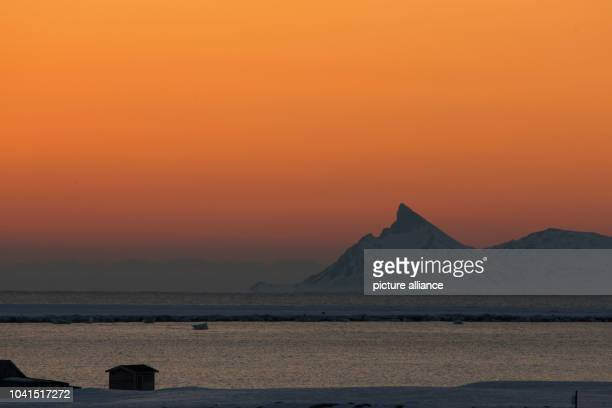 The sun sets just before midnight at the Kings Bay research station on Spitsbergen in NyAelesund Norway 09 April 2015 Scientists with the Alfred...