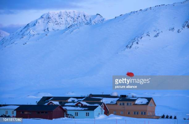 The sun sets just before midnight lighting up the settlement houses at the Kings Bay research station on Spitsbergen in NyAelesund Norway 09 April...