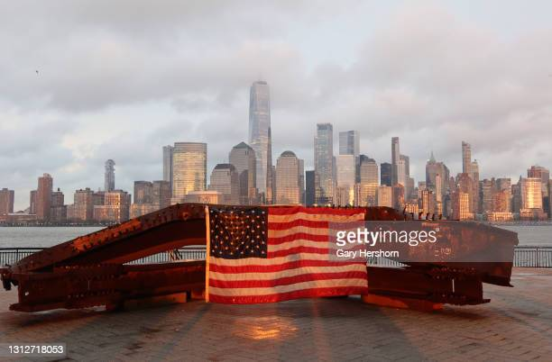 The sun sets on a flag hanging on a 9/11 memorial in front of the skyline of lower Manhattan and One World Trade Center in New York City on April 15,...