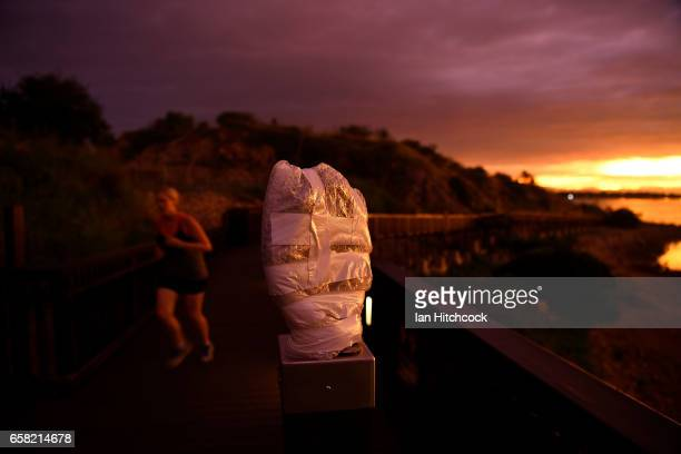 The sun sets on a piece of public art wrapped in bubble wrap for protection along a walkway at Kissing Point in preparation for Cyclone Debbie on...