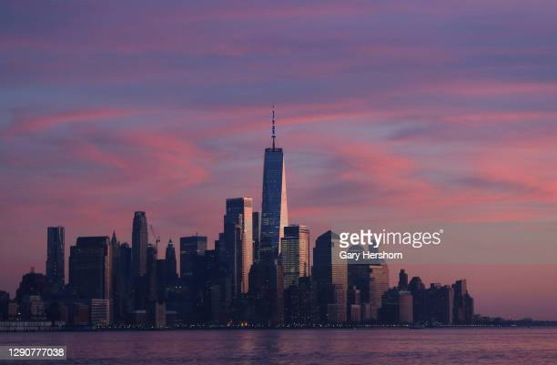 The sun sets on lower Manhattan and One World Trade Center in New York City on December 11, 2020 in Hoboken, New Jersey.