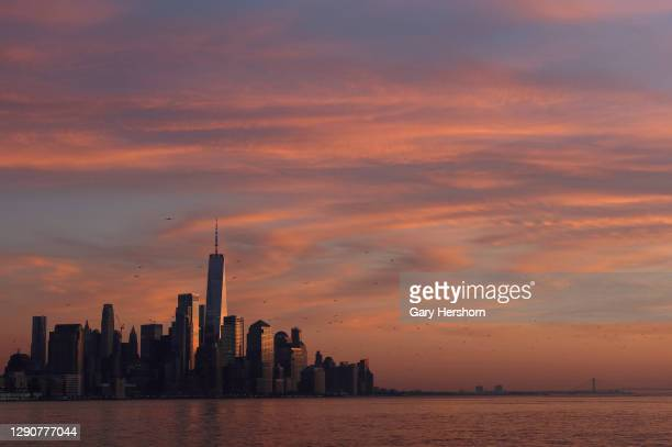 The sun sets on lower Manhattan and One World Trade Center in New York City on December 11, 2020 as seen from Hoboken, New Jersey.