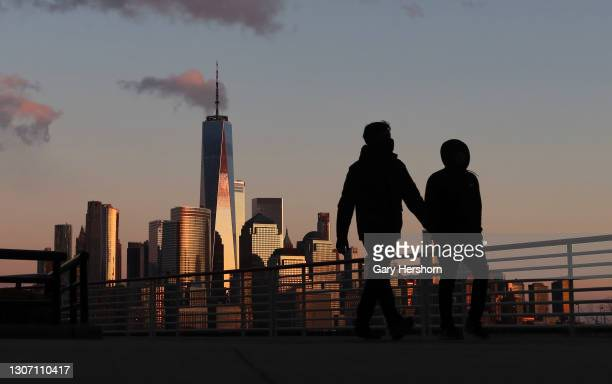 The sun sets on lower Manhattan and One World Trade Center in New York City on March 14, 2021 as seen from Jersey City, New Jersey.