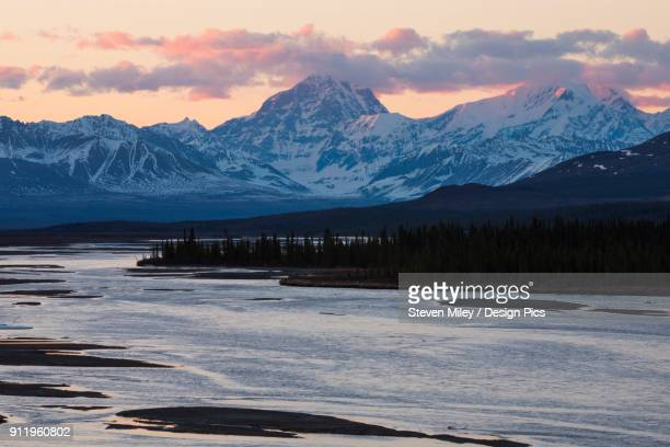 the sun sets on mt. deborah and mt. hess in the alaska range, viewed from the susitna river bridge along the denali highway - miley fotografías e imágenes de stock