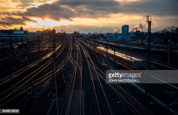 The sun sets on railway tracks in Berlin's Westhafen area on March 1 as an Sbahn train comes into a station / AFP PHOTO / John MACDOUGALL