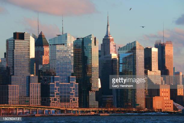 The sun sets on the buildings of Waterline Square along the West Side Highway and the Empire State Building in New York City on February 16, 2021 as...