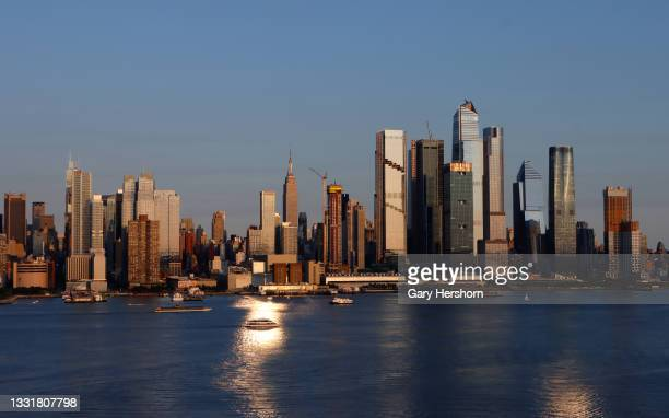 The sun sets on the Empire State Building, the Spiral and Hudson Yards in New York City on July 31, 2021 as seen from Weehawken, New Jersey.