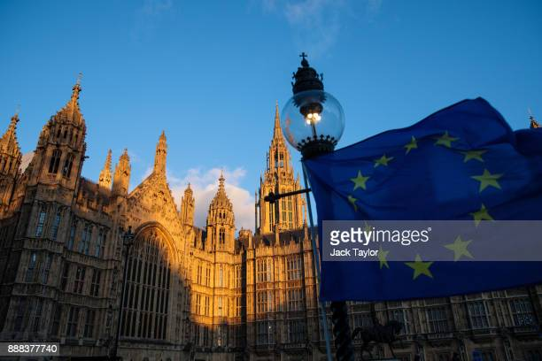The sun sets on the Houses of Parliament as an EU flag flutters in the wind on December 8 2017 in London England British Prime Minister Theresa May...