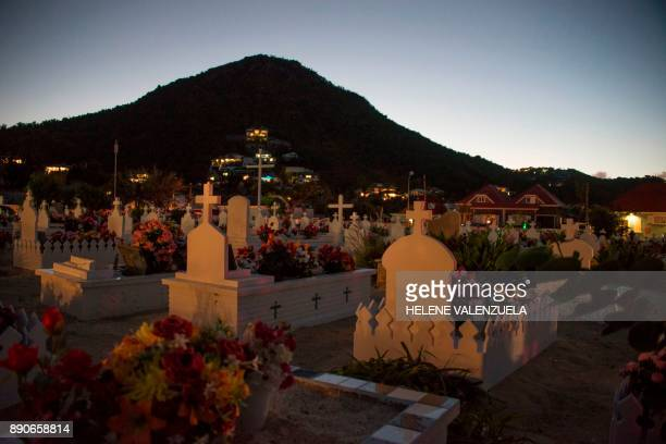 The sun sets on the Lorient Cemetery in Saint Barthélemy after the burial of French rock icon Johnny Hallyday on December 11 2017 Hallyday was laid...