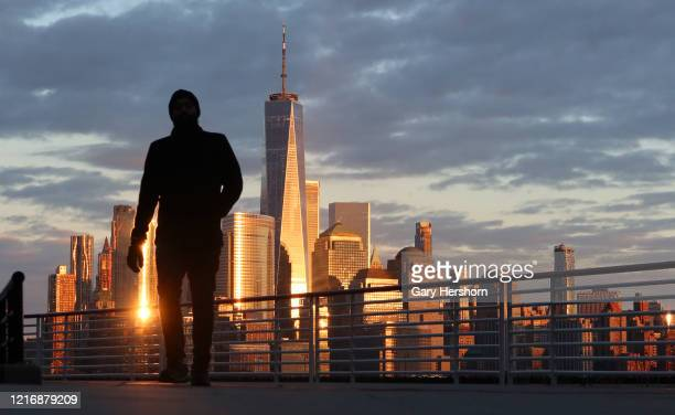 The sun sets on the skyline of lower Manhattan and One World Trade Center in New York City on April 4 2020 as seen from Jersey City New Jersey