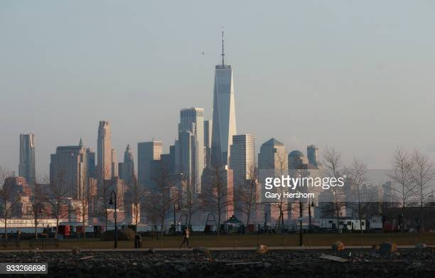 The sun sets on the skyline of lower Manhattan in New York City on March 15 2018 as seen from Hoboken New Jersey