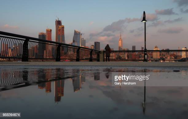 The sun sets on the skyline of midtown Manhattan Hudson Yards and the Empire State Building in New York City on March 15 2018 as seen from Hoboken...