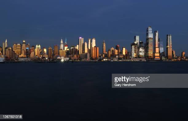 The sun sets on the skyline of midtown Manhattan in New York City on August 20, 2020 as seen from Weehawken, New Jersey.