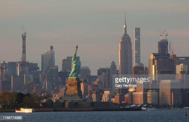 The sun sets on the skyline of midtown Manhattan the Statue of Liberty and the Empire State Building in New York City on June 9 2019 as seen from...