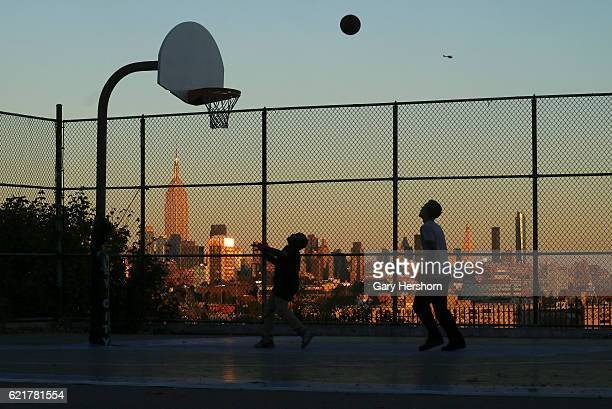 The sun sets on the skyline of New York City on November 4 2016 as children play basketball in Jersey City NJ