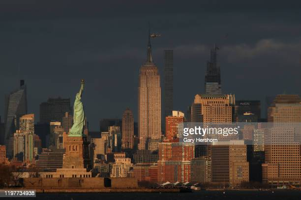 The sun sets on the Statue of Liberty as a helicopter flies over the Empire State Building in New York City on January 5 2020 as seen from Bayonne...