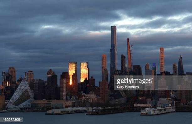The sun sets on the Time Warner Center, Central Park Tower and the Steinway Tower in New York City on March 6, 2021 as seen from Weehawken, New...