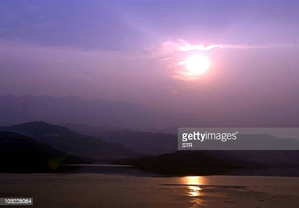 The sun sets on the Yangtze River near the Three Gorges dam in Yichang, central China's Hubei province, 04 June 2003. China's two biggest waterways...