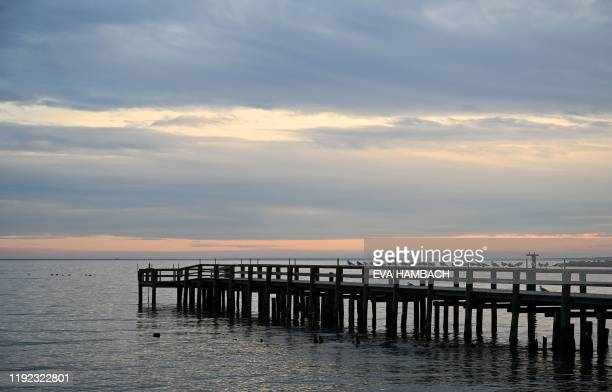 The sun sets over a fishing pier at Columbia Beach in Shady Side, Maryland, January 2, 2020. - The Chesapeake Bay, about 200 miles long, is located...