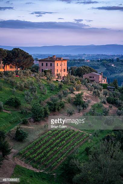 The sun sets over a pink stucco home and vineyard on the outskirts of Siena, Italy.