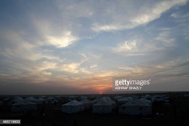 The sun sets over a refugee camp run by the Sudanese Red Crescent on January 26 2014 in the western part of Sudan's White Nile state about 30 kms...